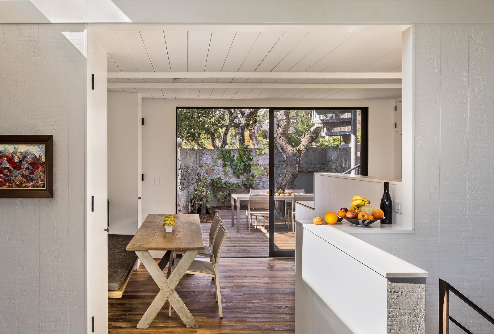 Guests now dine on a table from Coup d'Etat in the space where the residents used to enter the house. The dining room feels much larger than it actually is, thanks to a ten-foot-wide sliding glass door that opens onto a second, outdoor lounge.  Photo 6 of 10 in Bright Renovation of a 1970s Big Sur Home from Torres House