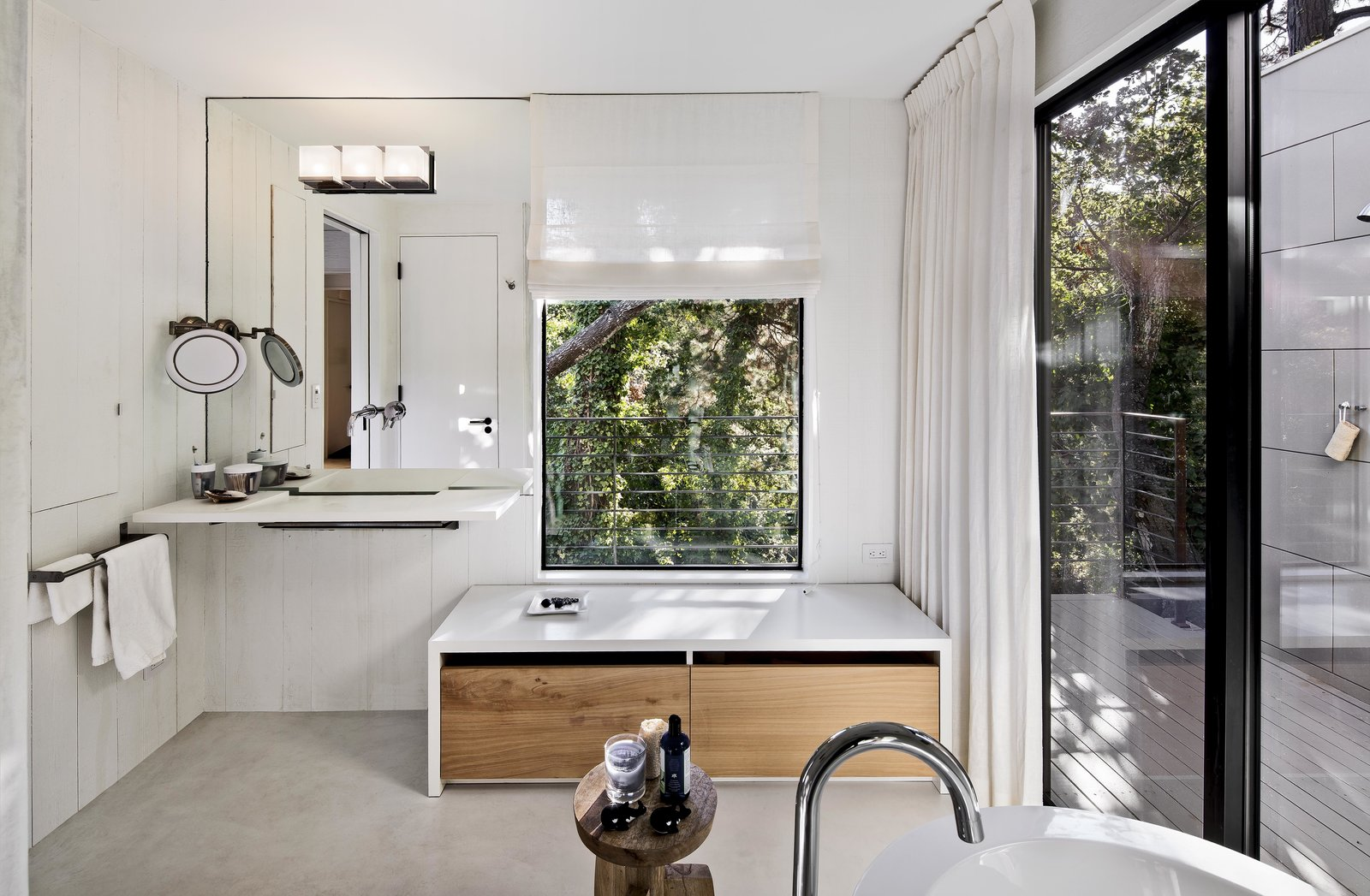 The updated master bathroom features white concrete floors, painted wood walls, and veneer plaster ceilings. Light streams in through the original window, and an added sliding door opens to an outdoor shower. A single Washplane sink by Omvivo sits beneath the mirror, with additional faucets for the shower and Duravit bathtub by Hansgrohe. A stool from Roost holds bath essentials.  Photo 5 of 10 in Bright Renovation of a 1970s Big Sur Home from Torres House