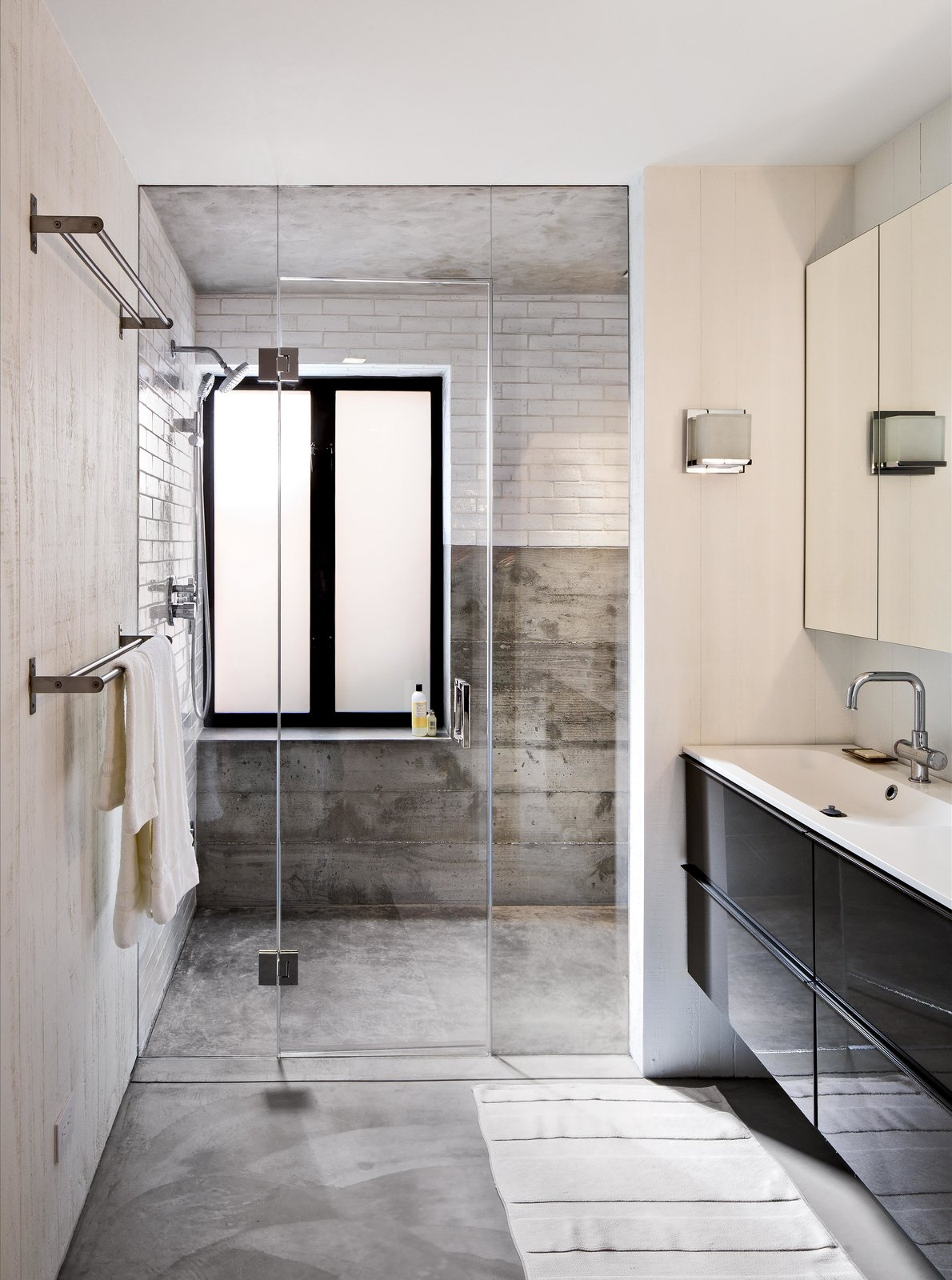 On the house's lower level, Schicketanz's guests have a bathroom complete with a steam shower to themselves. Anodized aluminum windows pop against white subway tile from Waterworks. The vanity is from Ikea and the fixtures from Hansgrohe.  Bathroom from Bright Renovation of a 1970s Big Sur Home
