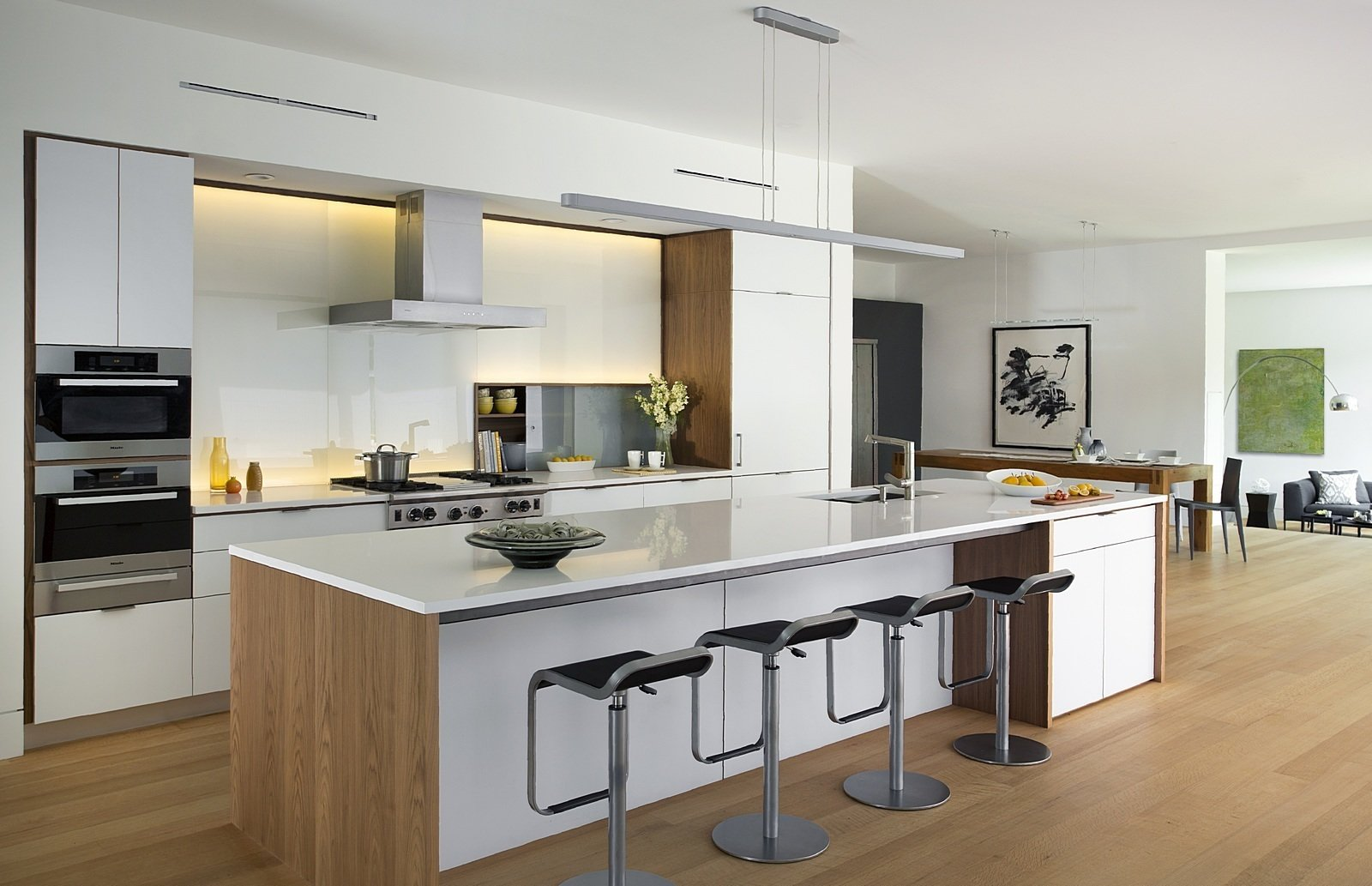 Kitchen, Engineered Quartz Counter, Refrigerator, Wall Oven, Cooktops, Range Hood, Range, Pendant Lighting, Light Hardwood Floor, and White Cabinet This kitchen features a sleek Henrybuilt kitchen system in white.  Photo 3 of 7 in A Modern Green Home in a Historic Colonial Town