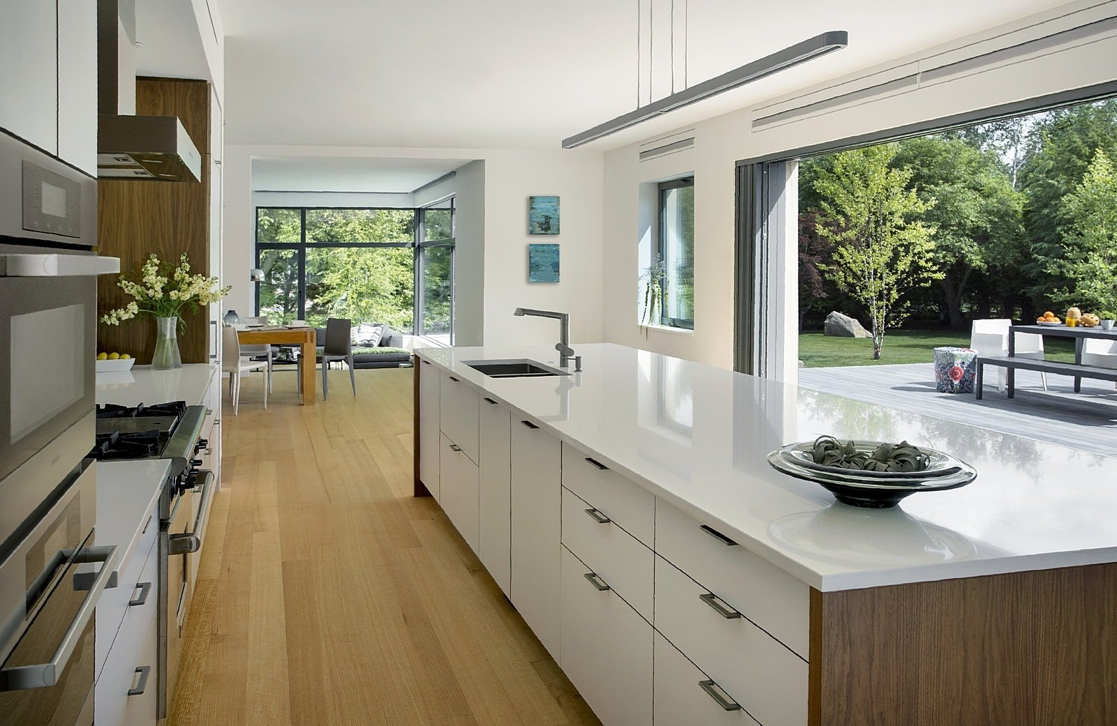 "Kitchen, Engineered Quartz Counter, White Cabinet, and Light Hardwood Floor A 22-foot-long door allows easy access to the backyard. ""We paired the lift and slide door with a retractable screen for insects and a retractable canopy above, to shade the deck and control heat gain into the house,"" Horowitz says.  Photo 4 of 7 in A Modern Green Home in a Historic Colonial Town"