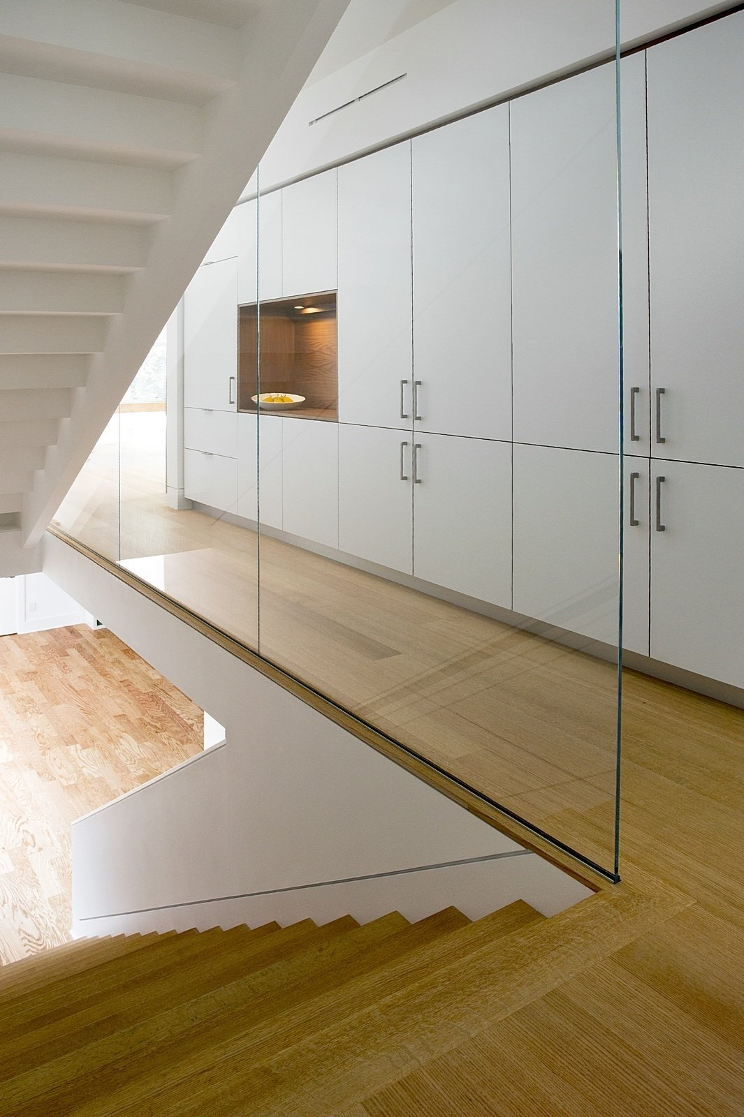 Staircase, Wood Tread, and Glass Railing A custom staircase with wood risers is encased by glass panels. A wall of Henrybuilt's kitchen system adds storage to the hallway.  Hallways That Impress from A Modern Green Home in a Historic Colonial Town