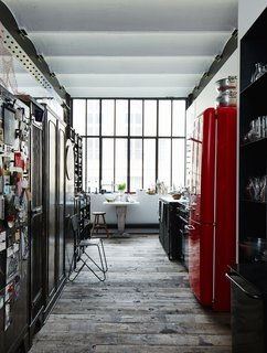 A Smeg refrigerator is one of a series of red accents that punctuate this black-and-white space.