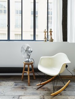 A vintage Eames rocking chair occupies a corner of the living room.