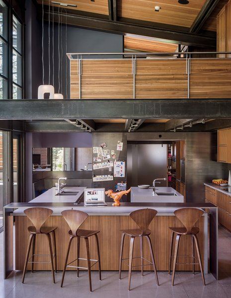 Norman Cherner barstools from Design Within Reach line the island in the kitchen, which is crowned by an open loft office. The faucets are from Dornbracht; the countertops are Caesarstone. Hawkins integrated a steel-clad casual eating nook, at left.