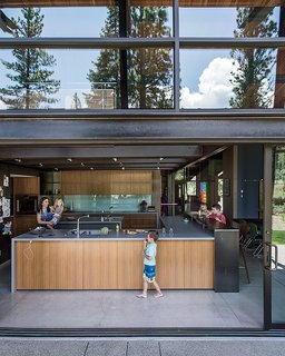 The kitchen opens to the elements thanks to sliding doors from C.R. Laurence. The anigre in the kitchen is the same employed in the master bedroom.