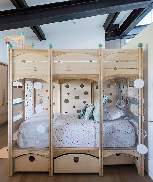 A sloping ceiling allows light into one of the children's bedrooms. The bed is from CedarWorks.