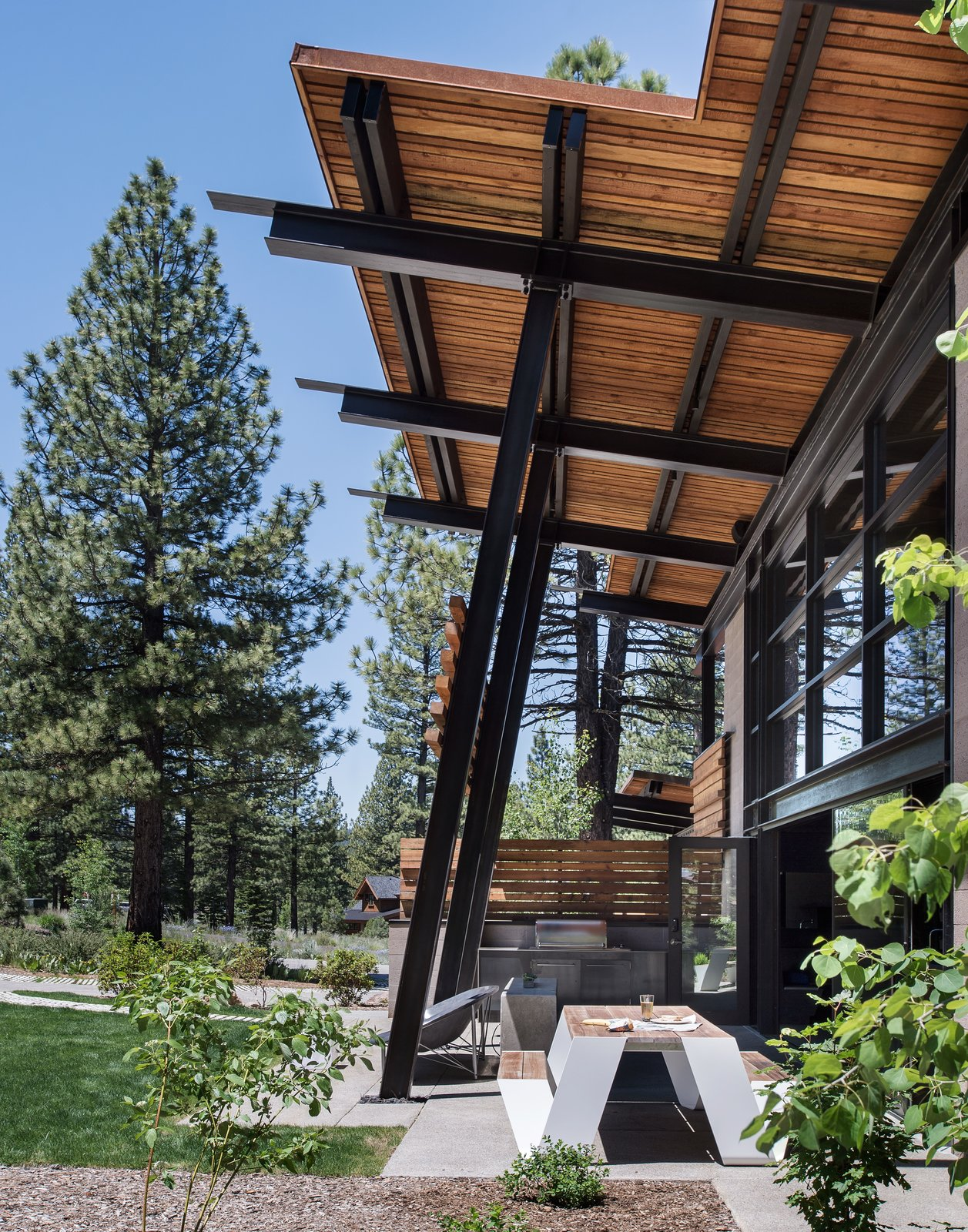 Outdoor, Back Yard, Trees, Grass, Walkways, Shrubs, Small Patio, Porch, Deck, Horizontal Fences, Wall, and Wood Fences, Wall You'd never designed for special needs children before the Bancroft residence, how did you interpret the clients' needs?  Jack Hawkins, architect: I would like to say I did tons of research, but I didn't. I went with the parents' lead. I took most of my design cues from them. They're the immediate caregivers, they know their children and about autism. They did all the research and told me what was important.  Photo 16 of 19 in A Forest Sanctuary Designed to Support Autistic Triplets, Their Parents, and a Host of Caregivers
