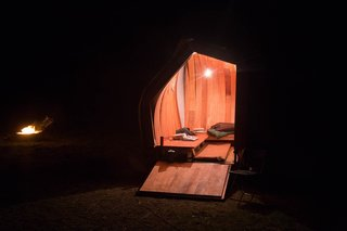 The team of 15 students and 5 professional volunteers then fabricated the home, seen here at night, using a mix of hand construction and power tools. Hand-made physical models were also part of the design process.