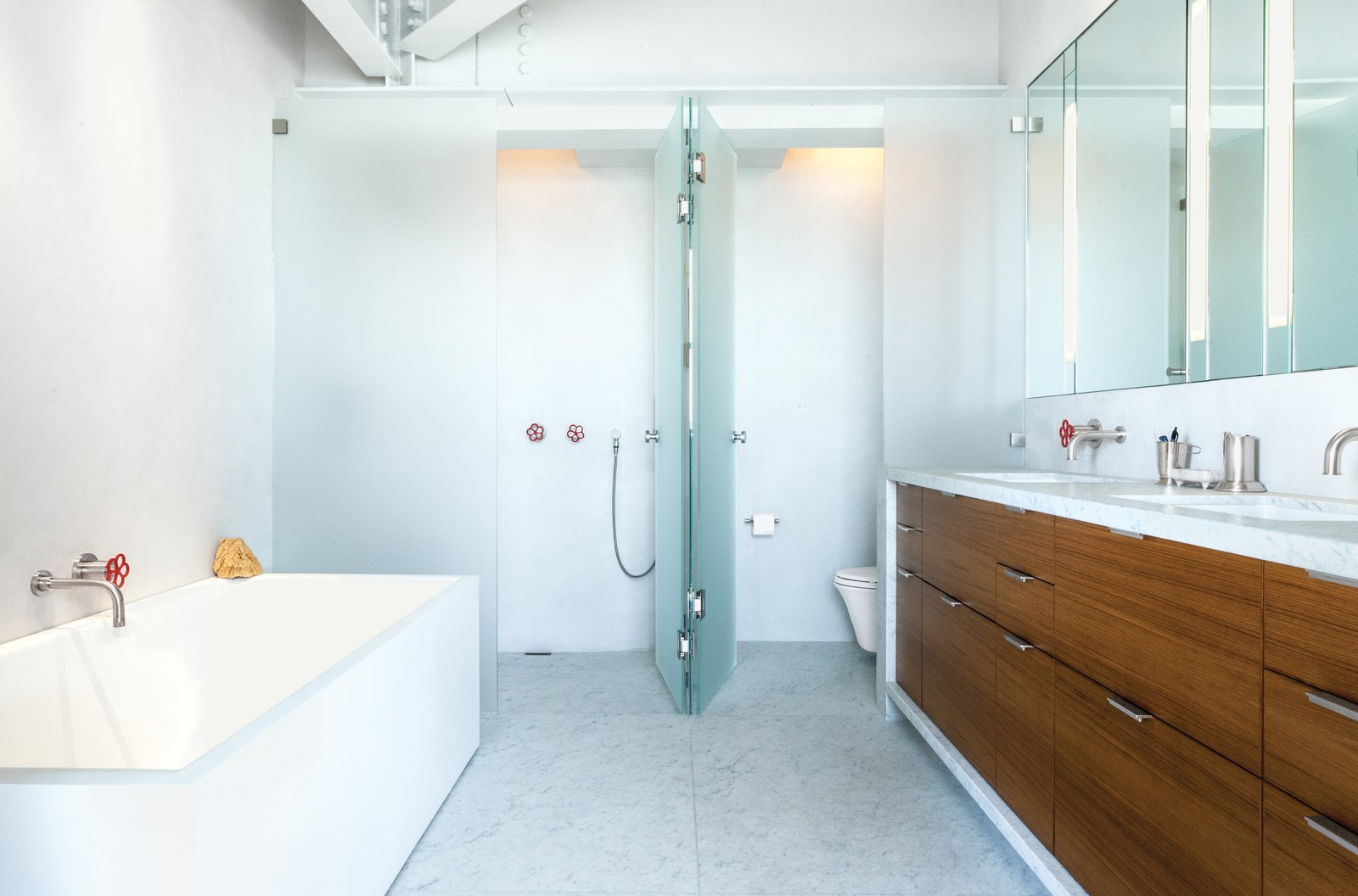 """""""The structural elements were left rough and exposed while the baths were designed to be clean and sleek,"""" Severns says. The bathroom is by Henrybuilt.  Parker Willis House by Erika Heet"""