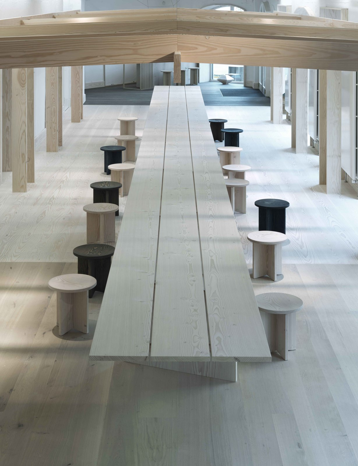 Custom stools can be pulled out to create a dining space. A wood pergola surrounds the table.  Photo 2 of 6 in Generations-Old Danish Wood Firm Dinesen Unveils Spiffy Copenhagen Showroom
