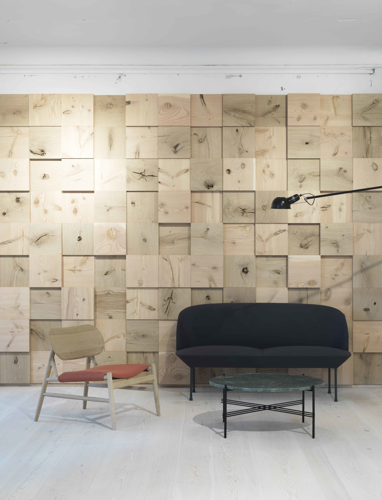 Though Dinesen typically does not use knotty wood, here those pieces are preserved and celebrated as a textured wall treatment. A sofa by Anderseen & Voll for Muuto sits next to a chair by OeO and Brdr. Krüger. The table is Gubi.  Photo 3 of 6 in Generations-Old Danish Wood Firm Dinesen Unveils Spiffy Copenhagen Showroom