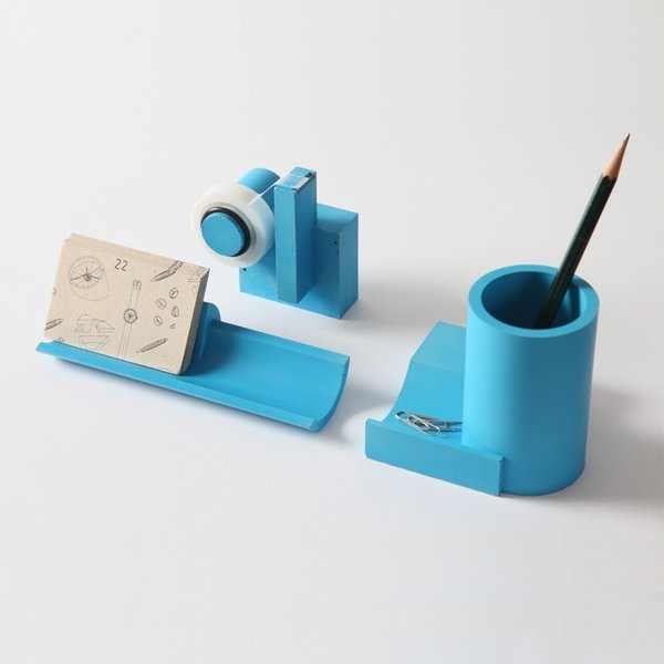 The Merge Concrete Desk Set is a collection of desktop items including a pen holder, cardholder tray, and tape dispenser. The Merge series is united by the enduring principles of geometry and the industrial appeal of concrete.