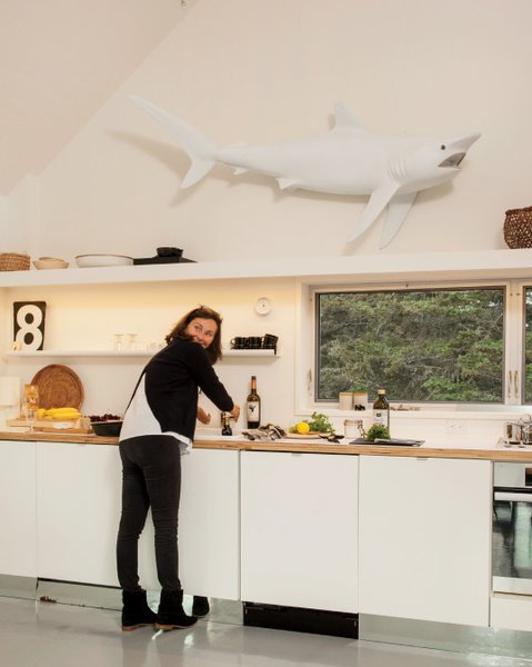 In the kitchen, a sculptural replica of a shark hangs above the sink.