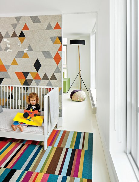 A bunny mobile by Flensted hangs over the crib, while the felt mural provides a soft and colorful backdrop. The Excel floor lamp in the living room is by Rich Brilliant Willing.