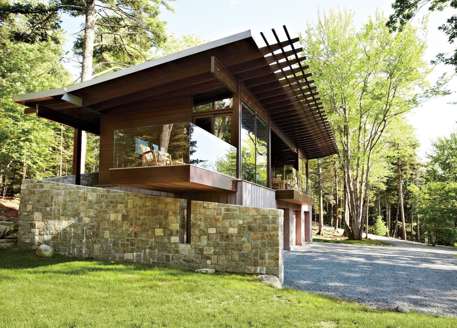 "Exterior, Metal Roof Material, House Building Type, and Wood Siding Material From its locally quarried stone foundation to its zinc-coated copper roof, the cottage was inspired by its surroundings. ""We talked a lot with our client about what the materiality would be,"" says architect Karen Stonely, who, citing the organic style of Bar Harbor architect Robert Patterson, designed the structure with wood rather than drywall.  Photo 1 of 5 in Frank Lloyd Wright-Inspired Style and Camping Collide in Maine"