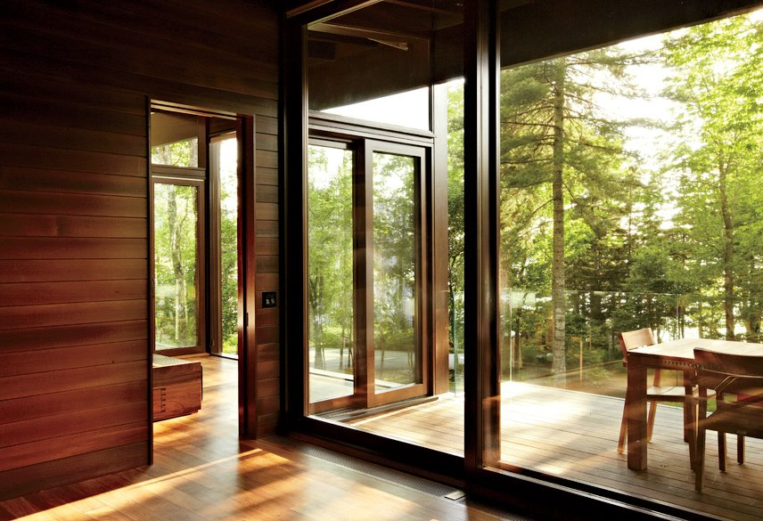 Windows, Wood, and Sliding Window Type Douglas fir-framed windows by Dynamic Architectural Windows & Doors offer layered indoor-outdoor views.  Photo 3 of 5 in Frank Lloyd Wright-Inspired Style and Camping Collide in Maine
