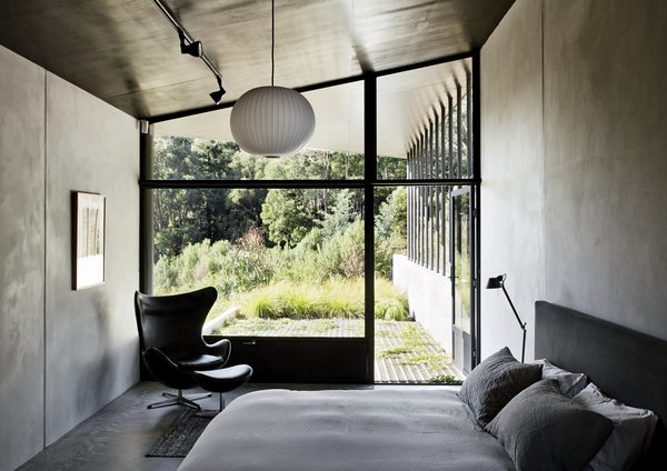 The master bedroom, which features a bed by Paolo Piva, an Egg chair by Arne Jacobsen, and a Ball pendant lamp by George Nelson, opens directly onto a verdant patio. The metal shutters at the bottom of the window keep out flying embers in case of fire.