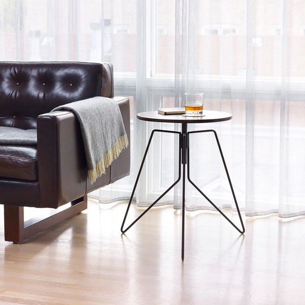 Coleman End Table is an innovative table that blends a sleek black powder coated frame with a sophisticated solid black walnut tabletop. The top is supported by three geometric base supports that give the table a sculptural look and feel. The tabletop adjusts from 22 to 28 inches in height, making it a multifunctional option for a variety of interior spaces.