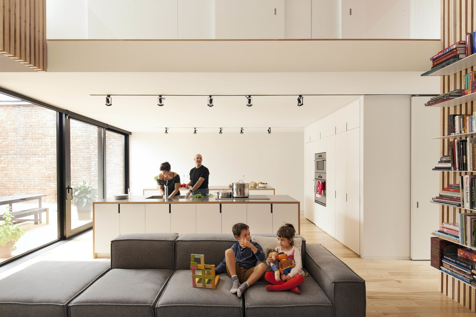 "The architects arranged the ""service areas"" of the home—closets, a bathroom, storage space, and most of the kitchen appliances—in a block near the entrance, a move that allows for clear views across the open-plan kitchen and living areas.  Photo 4 of 15 in A Transformative Duplex Renovation in Montreal"