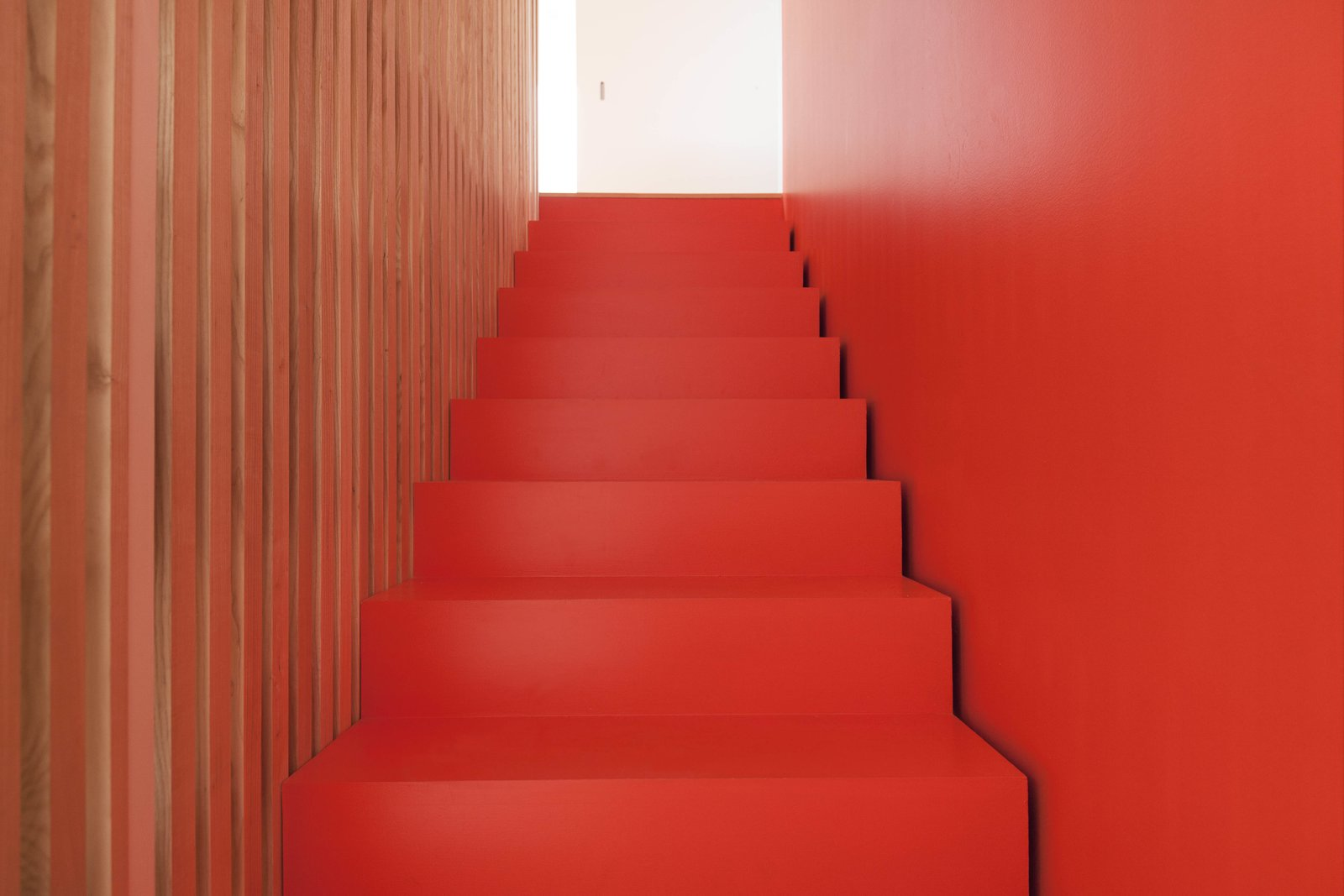 The stairs are coated in orange lacquer.  190+ Best Modern Staircase Ideas from A Transformative Duplex Renovation in Montreal