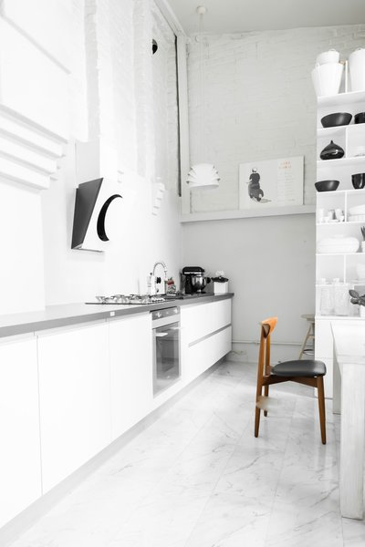 In this kitchen, an exposed brick wall stands out against the milky smoothness of the marble tile floors.