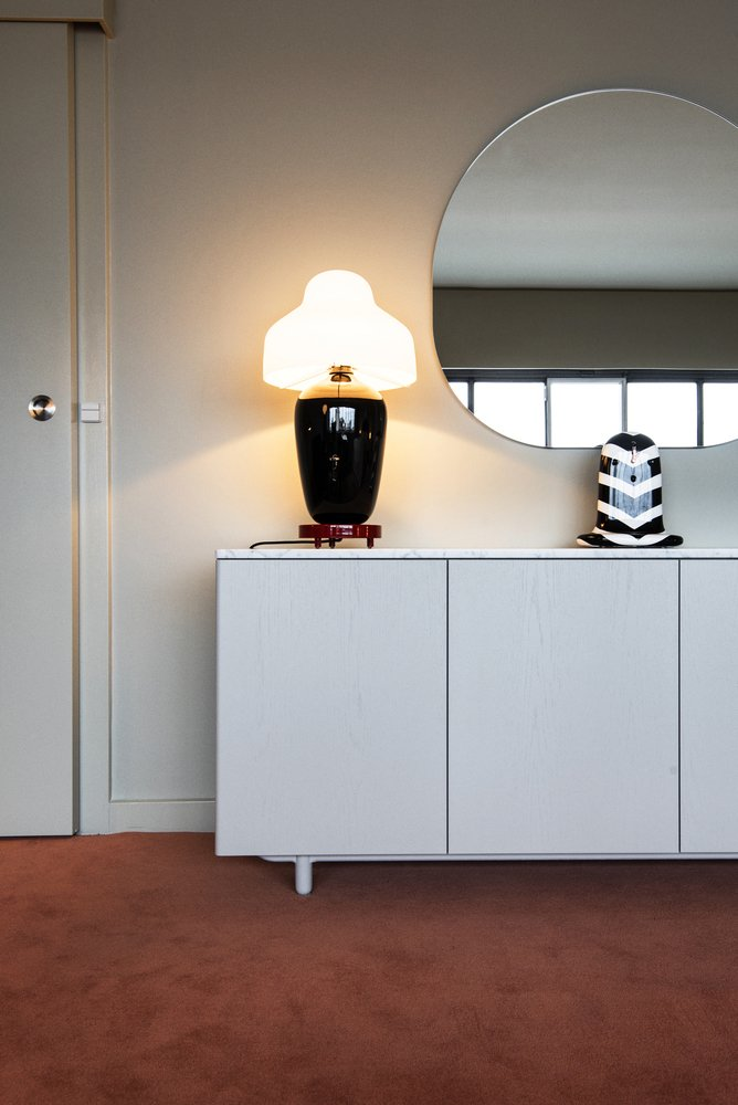 """Hayon used a color palette inspired by the hotel's past incarnations when designing the room. """"I used color with a bit of contrast,"""" he says. """"Tones that had a big charge of grey—blue grey, pink grey etc.—and played with materials such as modern velvets and fine Danish textiles. The tones make the room elegant; the space feels peaceful, relaxing, easy, and cozy. To me, this brings back to a sort of 'Royal' look but in a very modern way."""" The ceramic Chinoiz table lamp is by Parachilna.  Photo 6 of 10 in Jaime Hayon Reimagines a Room in an Iconic Copenhagen Hotel"""