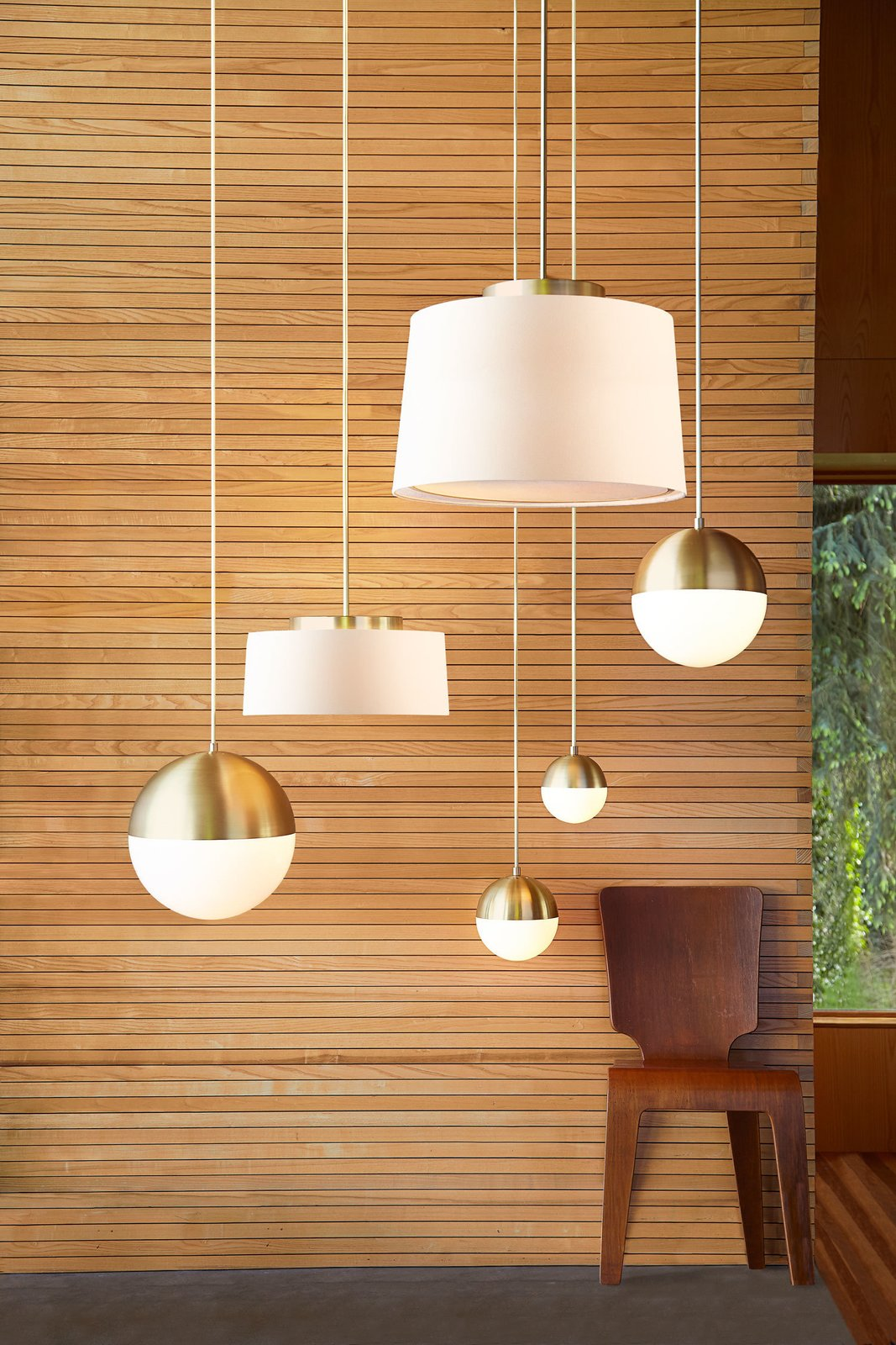 Living Room, Pendant Lighting, and Chair The collection combines influences from modernism and the Arts and Crafts movement. The Cedar & Moss pendants with a brushed satin finish are shown here.  Photo 3 of 7 in Classic Modernist House in Portland Inspires a Lighting and Furniture Line