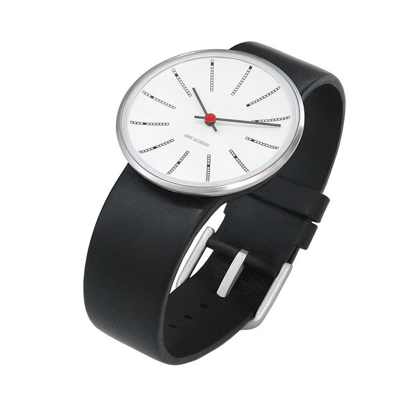 The AJ Banker's Watch from Rosendahl follows in the tradition of Arne Jacobsen's iconic Banker's Wall Clock, which was originally designed for the Danish National Bank in 1971. This wristwatch expertly captures the wall clock's distinctive markers, simple hands, and striking red center. As with Arne Jacobsen's wall clocks, the dial and curved crystal of the case comprise a single unit, with movement located at the back of the watch.