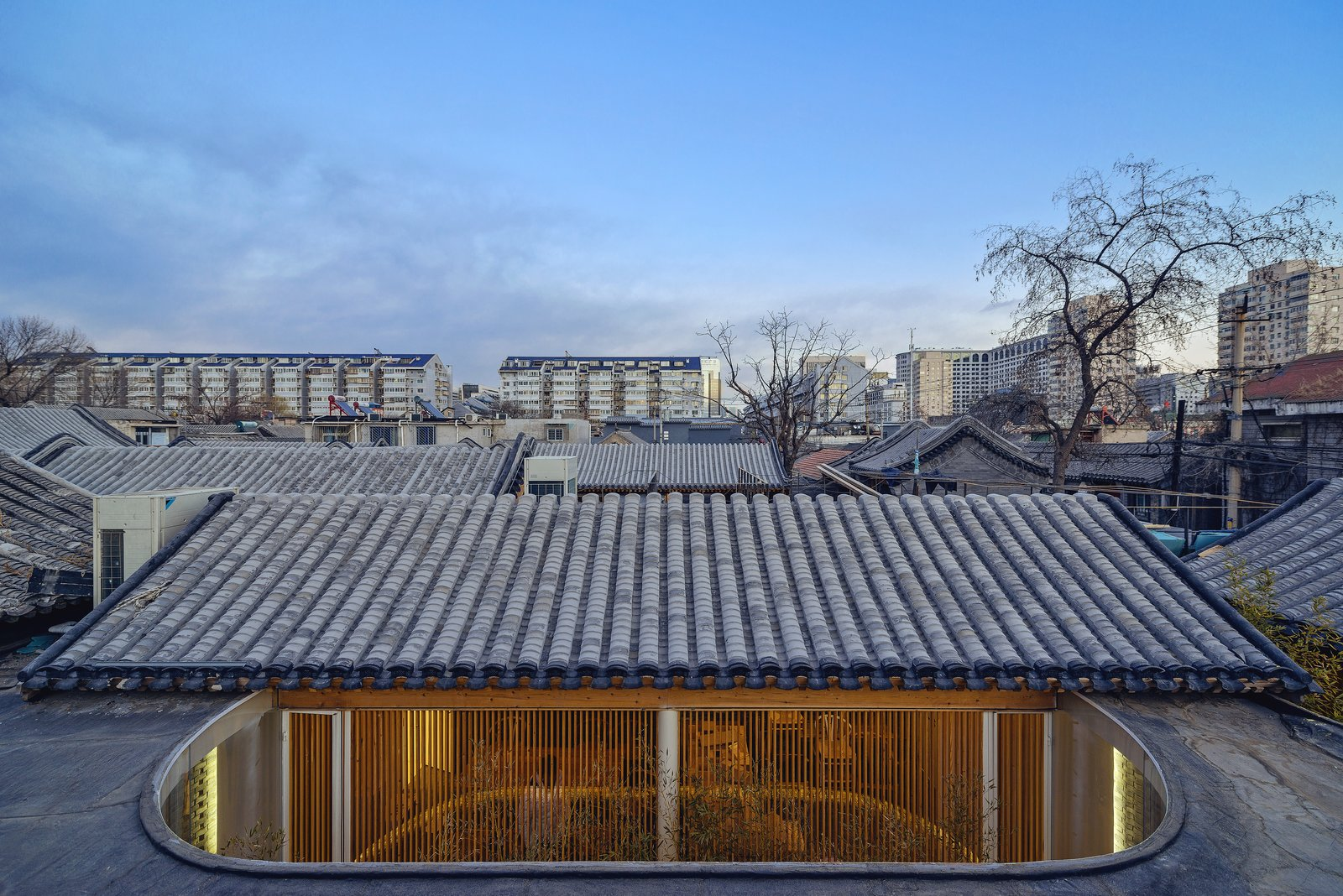 The roofs were also renovated but maintain their traditional pitched roofs. The new glass enclosure can be seen below.  Photo 4 of 7 in A Historic Beijing Structure Gets a Modern Makeover