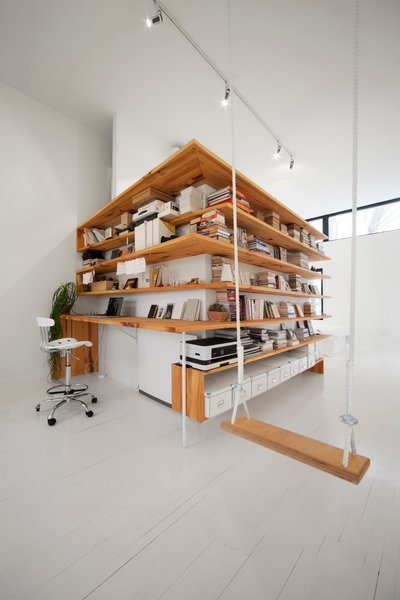 The renovated attic is oriented around a central volume that houses the bathroom. The wooden shelves were fashioned from hemlock planks that were salvaged during the demolition of the roof structure.