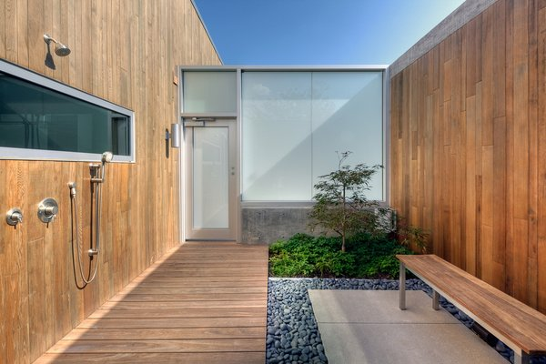 The outdoor shower situated off of the master bedroom is enclosed to offer privacy and features a courtyard garden. Michael Arp of Lanoha Nurseries designed the house's landscaping.