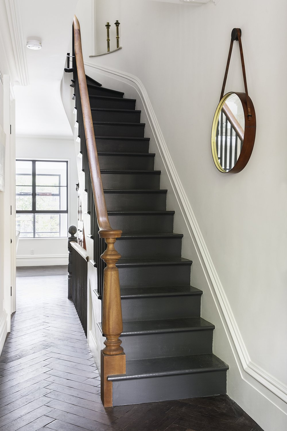 Reclaimed oak with a custom finish by LV Wood surrounds a staircase in a herringbone pattern. The new stairs are painted off black by Farrow & Ball, and the handrail that lines them is of salvaged mahogany.  190+ Best Modern Staircase Ideas from A Neglected Brooklyn Townhouse Becomes a Home That's Primed for Entertaining