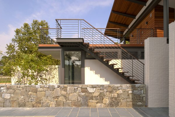 """The roof deck, reachable by outdoor stairs, affords """"the best view of the river"""" on the property, says architect Mark McInturff. The original stone wall divides the house's indoor and outdoor spaces."""