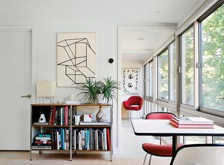 A print by the abstract expressionist Al Held hangs above a storage unit by Charles and Ray Eames for Herman Miller. The table lamp is by Isamu Noguchi, and the cork floor tiles are from Globus Cork. A Saarinen Executive Arm Chair is at the end of the hall.
