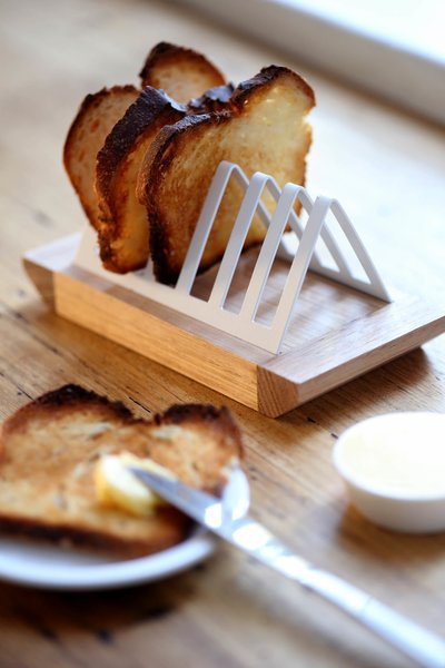 """""""We find ourselves in the marginal group who still love a simple slice of toast and decided to design something to emphasize this as well as solve a problem that hasn't been addressed for a good 20 to 30 years,"""" Pedersen says of this toast rack. """"The size and shape of bread has changed, and so we found that our old inherited toast racks didn't work anymore! Our solution is a simple combination of a wooden breadboard base with a steel or brass rack, which clips in nicely and holds toast [slices] of varying thickness."""""""