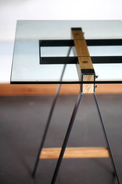 "The Glass Trestle table ""explores the relationship between steel and wood to complement each other in a way that each material is intrinsically weak without the other,"" Pedersen says. ""The wood is clamped between the steel, which in turn holds the structural steel that supports the weight of the glass as it spans. The manufacturing process interests us a lot as the parts are individually cut out and welded together, but the strength only comes when the parts are assembled. We've done a range of sizes for this table, from a small home office desk to a larger boardroom table."""