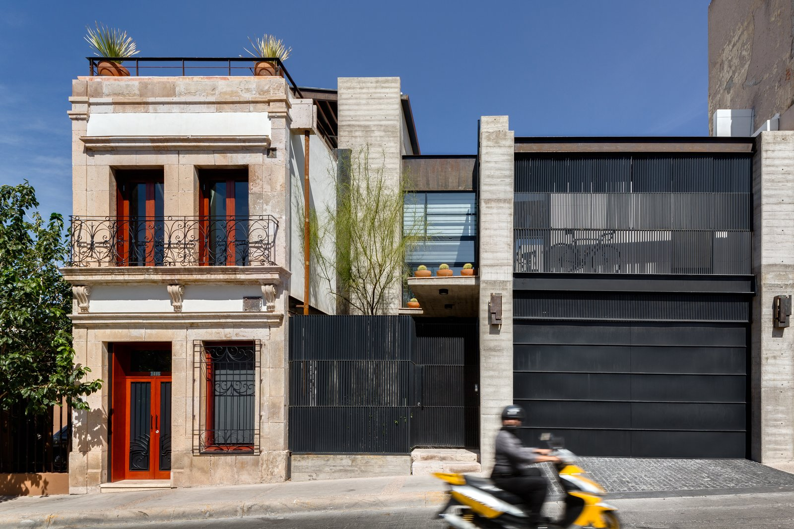 """The early-20th-century structure is seen next to the 300 square meter modern addition. A garage and patio were added, as well as a balcony that would complement the proportions of those in the original building. According to Quevedo, the biggest challenge was to approach both structures with a """"common language"""" and explore the idea that """"preservation and modernity can coexist.""""  Hybrid Home by Sarah Akkoush"""