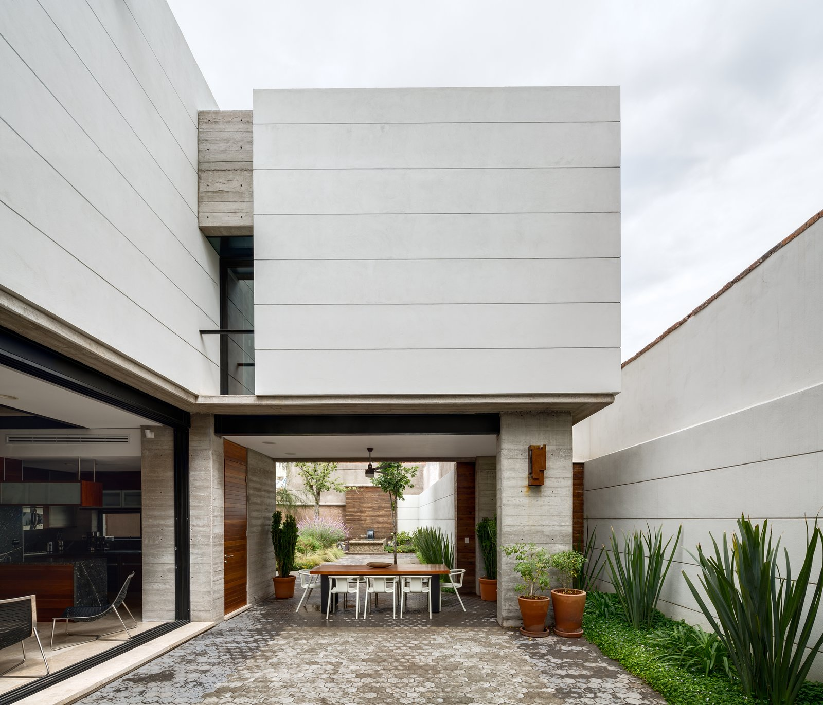 Outdoor and Side Yard The open and airy courtyard and dining area encourages outdoor living. A custom table made from Andiroba wood and Magis White Air armchairs complete the space.  Photo 7 of 11 in 10 Retreats in Mexico For the Modernists Who Love the Outdoors from Hybrid Home