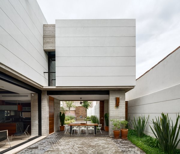 Outdoor and Side Yard The open and airy courtyard and dining area encourages outdoor living. A custom table made from Andiroba wood and Magis White Air armchairs complete the space.  Indoor-Outdoor Retreats in Mexico by Allie Weiss from Hybrid Home