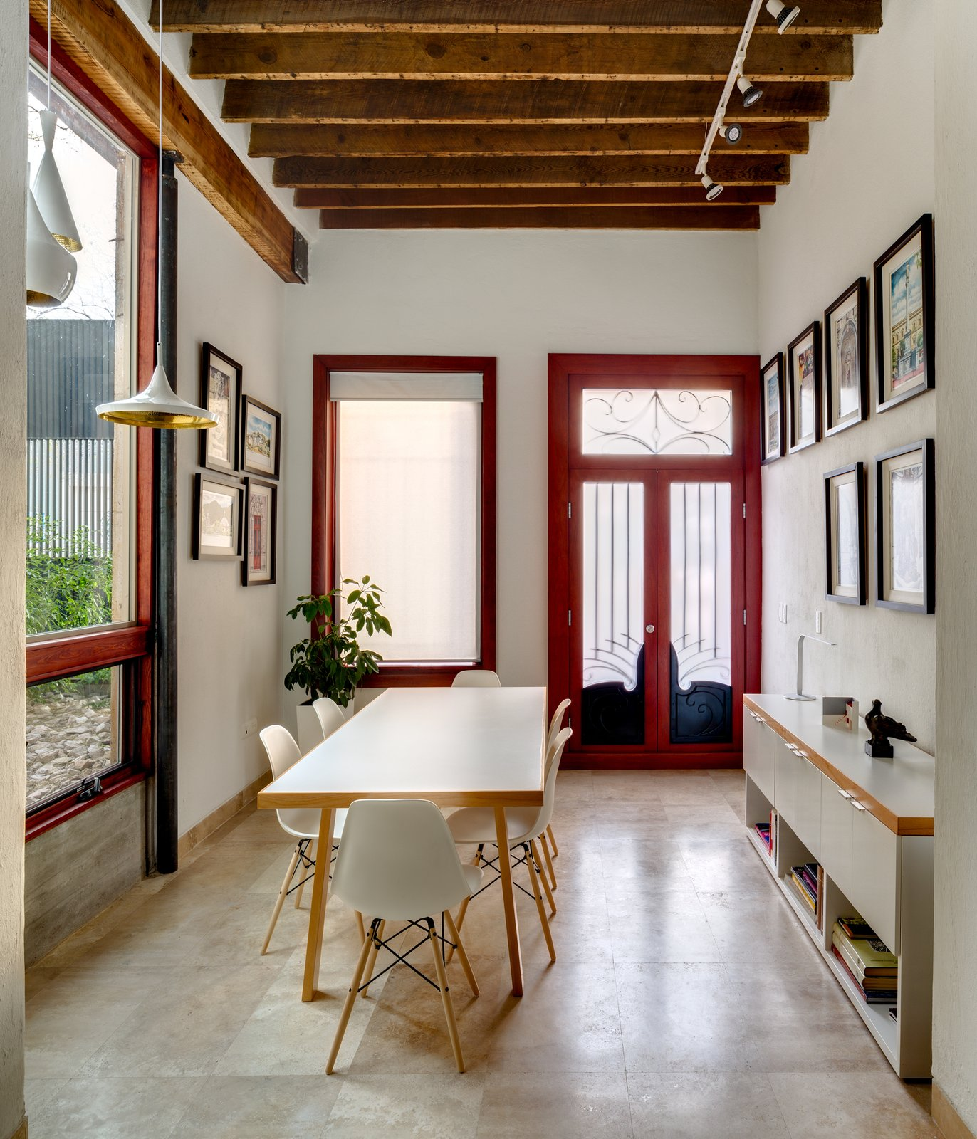 In the old building, the painting studio is accessible from the patio. At the center of the space, a custom table is flanked by Eames shell chairs. Tom Dixon pendant lamps hang from rustic wood beams, and a Pablo Studio Lim360 table lamp sits atop a custom white cabinet.  Hybrid Home by Sarah Akkoush