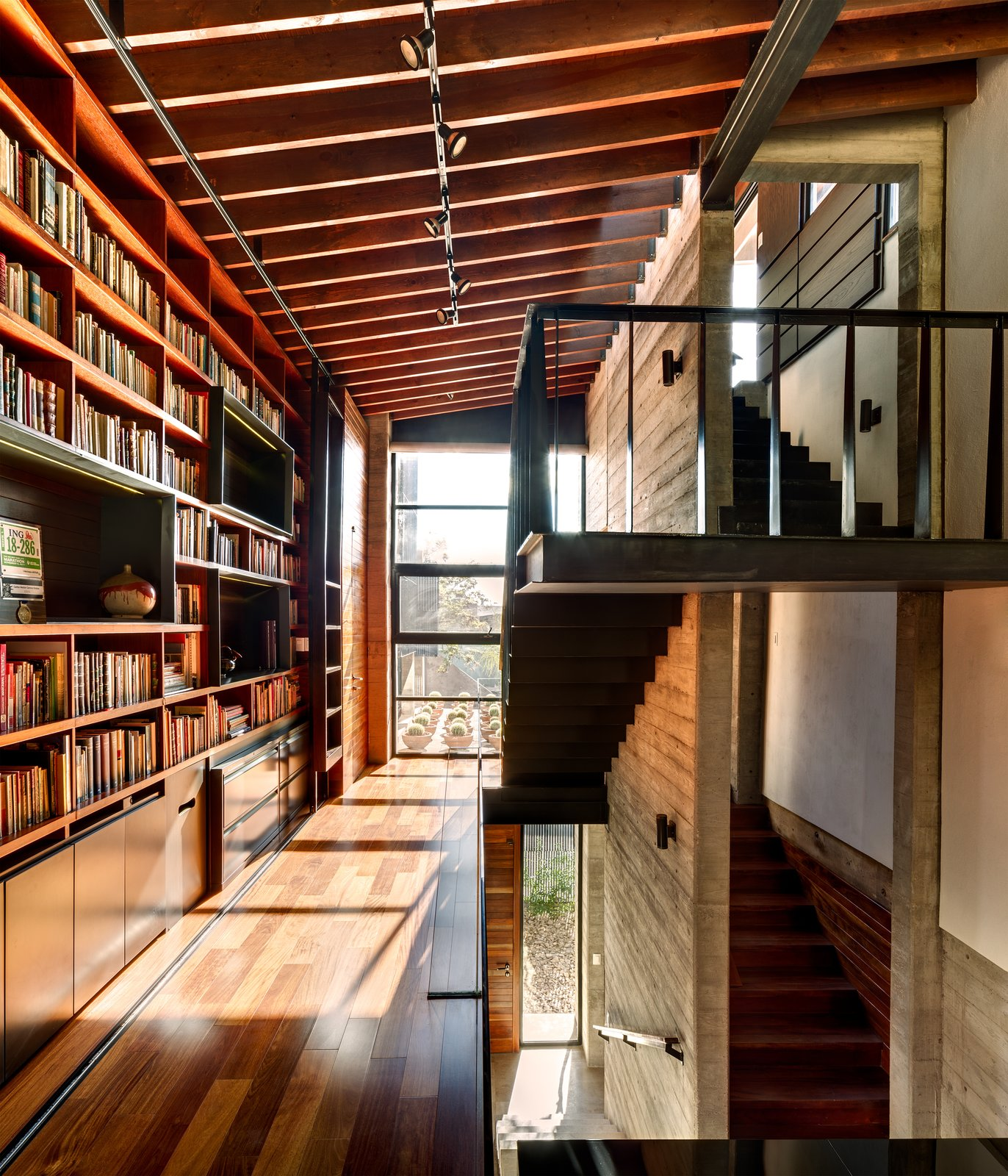 Suspended over the living room, the library bridge connects the second floor rooms of the house. The transitional space contains built-ins and desks where the owners and their three-year-old daughter can sit and read. The steel of the staircase is supported entirely by the adjacent concrete wall. A marriage of concrete, wood, and glass is used in the space, and the large windows let light in and offer a view of the roof garden.  Hybrid Home by Sarah Akkoush