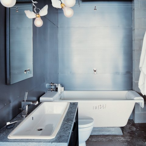When designer Barbara Hill decided to renovate her 1960s condo in Houston, Texas, she stripped the bathroom down to its bare bones and saw beauty in the blemishes. photos by: Dean Kaufman  Bathroom from Ways to Use Concrete in the Bathroom