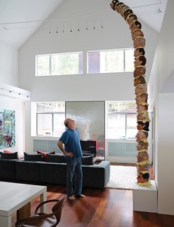 Andrew Weinstein stands in the living room of his Long Island abode designed by Bates Masi + Architects. The architects toggled wall panels and panes of custom-cut window glass on the front of the house that let in light while leaving room for large-format artwork like Adam Parker Smith's American Totem.