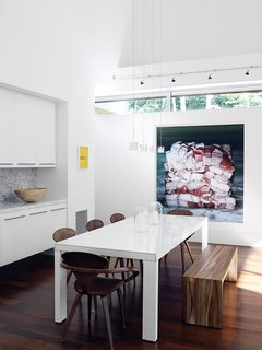 A white lacquer Ligne Roset dining table is joined by a wood bench from Room & Board and bent-plywood Cherner chairs. Baconcube 4 by Cindy Wright hangs on the wall.
