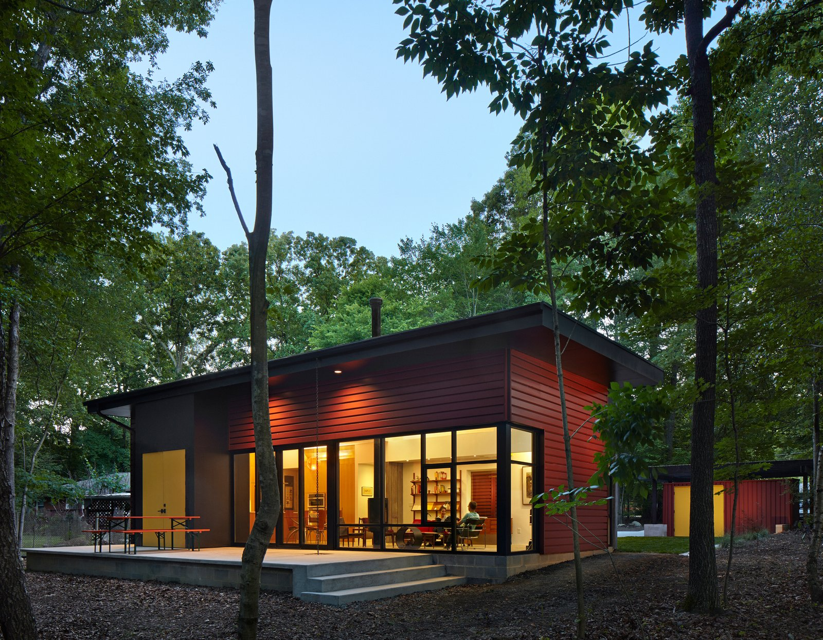"""Exterior, Metal Siding Material, and House Building Type Nestled in a forest, the residence consists of three volumes. The patio, enhanced by a German-made beer garden table, is an extension of the living room floor, creating an indoor-outdoor living space. """"It's one way a small space can be made to feel larger,"""" says architect Jason W. Hart. All of the exterior doors are painted marigold, providing a friendly pop of color.  Search """"staircasetread--metal"""" from This Light-Filled Metallic Home Embraces Its Wooded Site"""