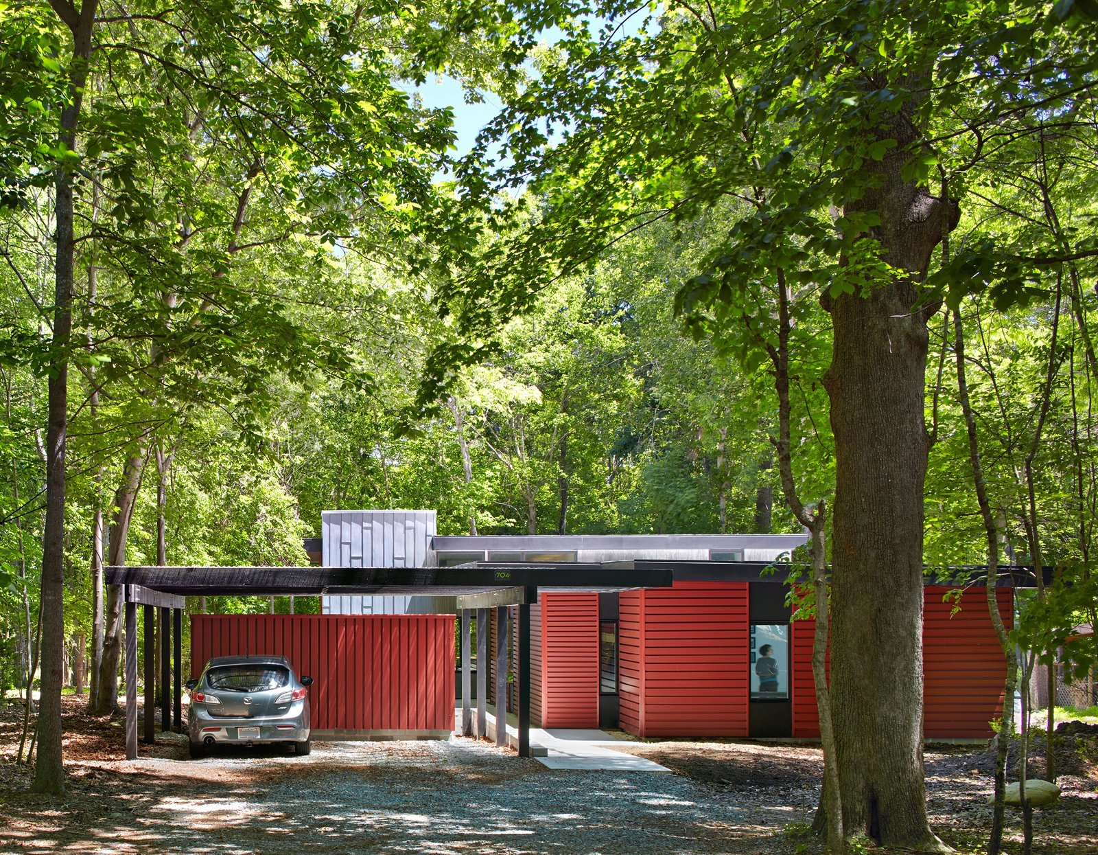 "Exterior, House Building Type, and Metal Siding Material Topped with translucent polycarbonate roof panels, the carport and storage shed helps buffer the home from the road. ""It's part of easing into the site with increasing enclosure along the entry axis,"" Hart says. ""We created a purposefully drawn-out experience that's intended to heighten awareness of the site and gradually transition from the forest to the home.""  Photo 2 of 8 in This Light-Filled, Metallic Home Embraces Its Wooded Site from This Light-Filled Metallic Home Embraces Its Wooded Site"
