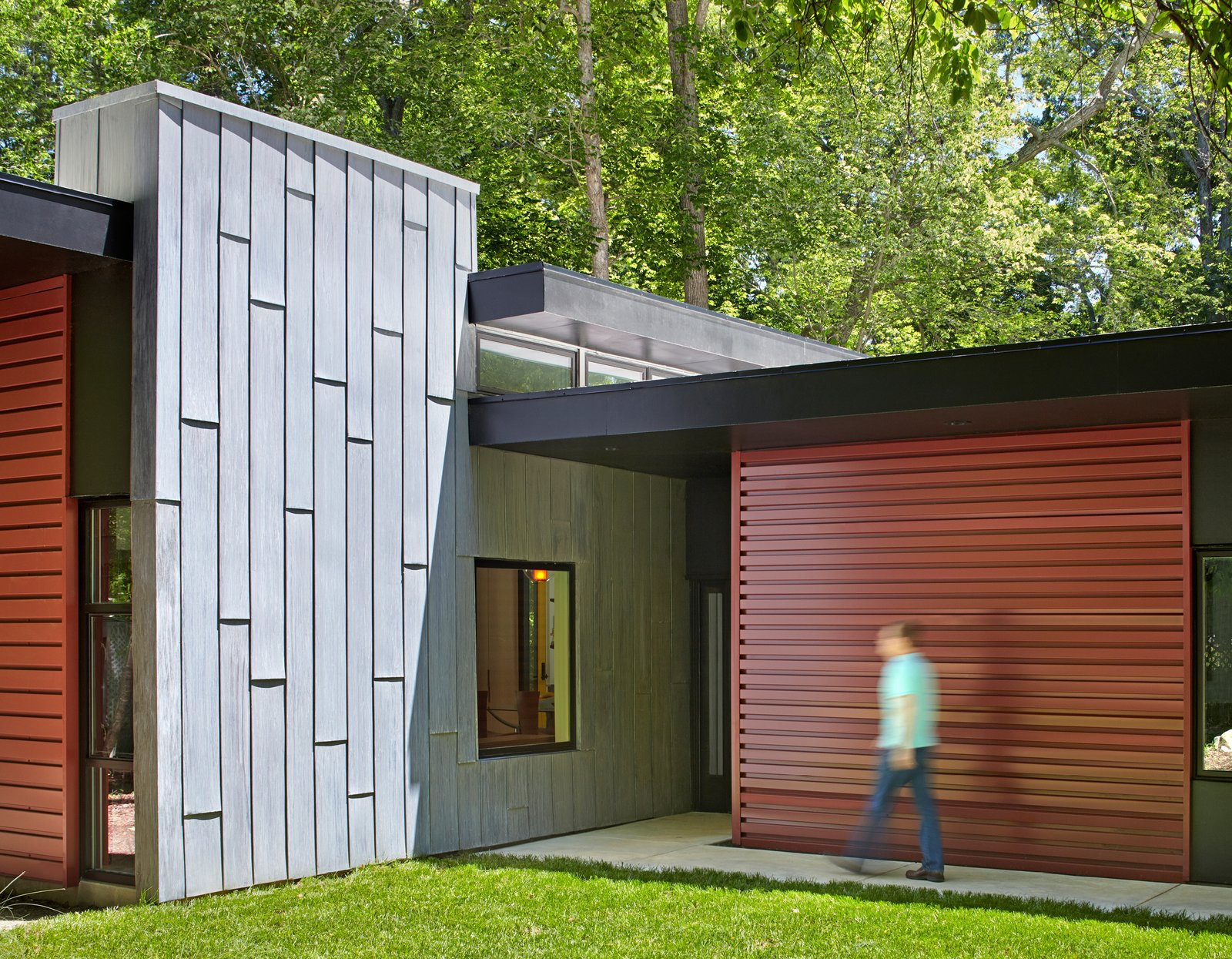 Exterior, House Building Type, and Metal Siding Material A tall gray wall, made of acid-washed zinc metal, marks the entryway and visually grounds the roof planes. It also separates the living and bedroom volumes.  Photo 4 of 8 in This Light-Filled, Metallic Home Embraces Its Wooded Site from This Light-Filled Metallic Home Embraces Its Wooded Site