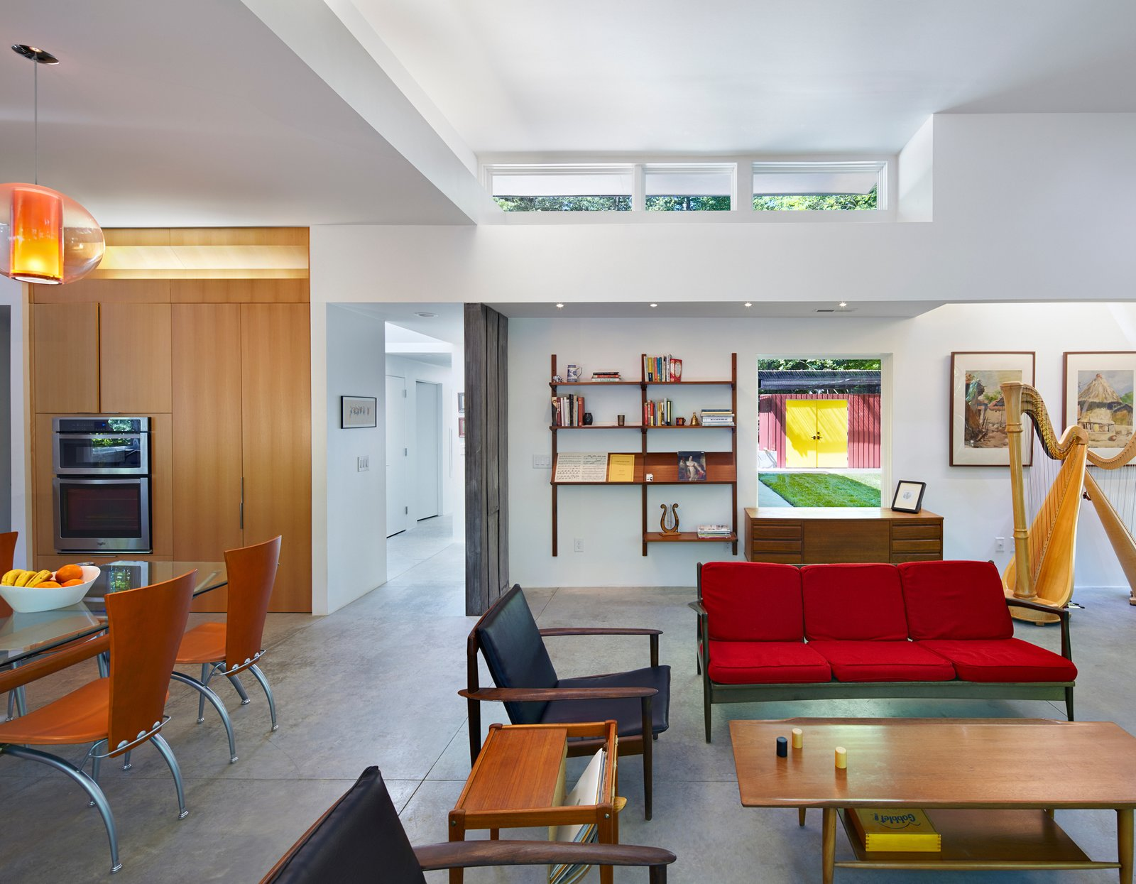Living Room, Sofa, Chair, and Concrete Floor The Aiyyers' midcentury furniture collection adds personality and color to the open-plan interior. A sofa by Kofod-Larsen for Selig, chairs by Viko Baumritter, shelving by Regner Christensen, and a coffee table by a local craftsmen accentuate the living room, while a dining table and chairs by Calligaris, custom cabinetry with pulls by Mockett, and an overhead Bel Occhio light from Pablo Designs complete the kitchen. Leigh's harp, from Lyon & Healy, sits nearby.  Photo 5 of 8 in This Light-Filled, Metallic Home Embraces Its Wooded Site from This Light-Filled Metallic Home Embraces Its Wooded Site