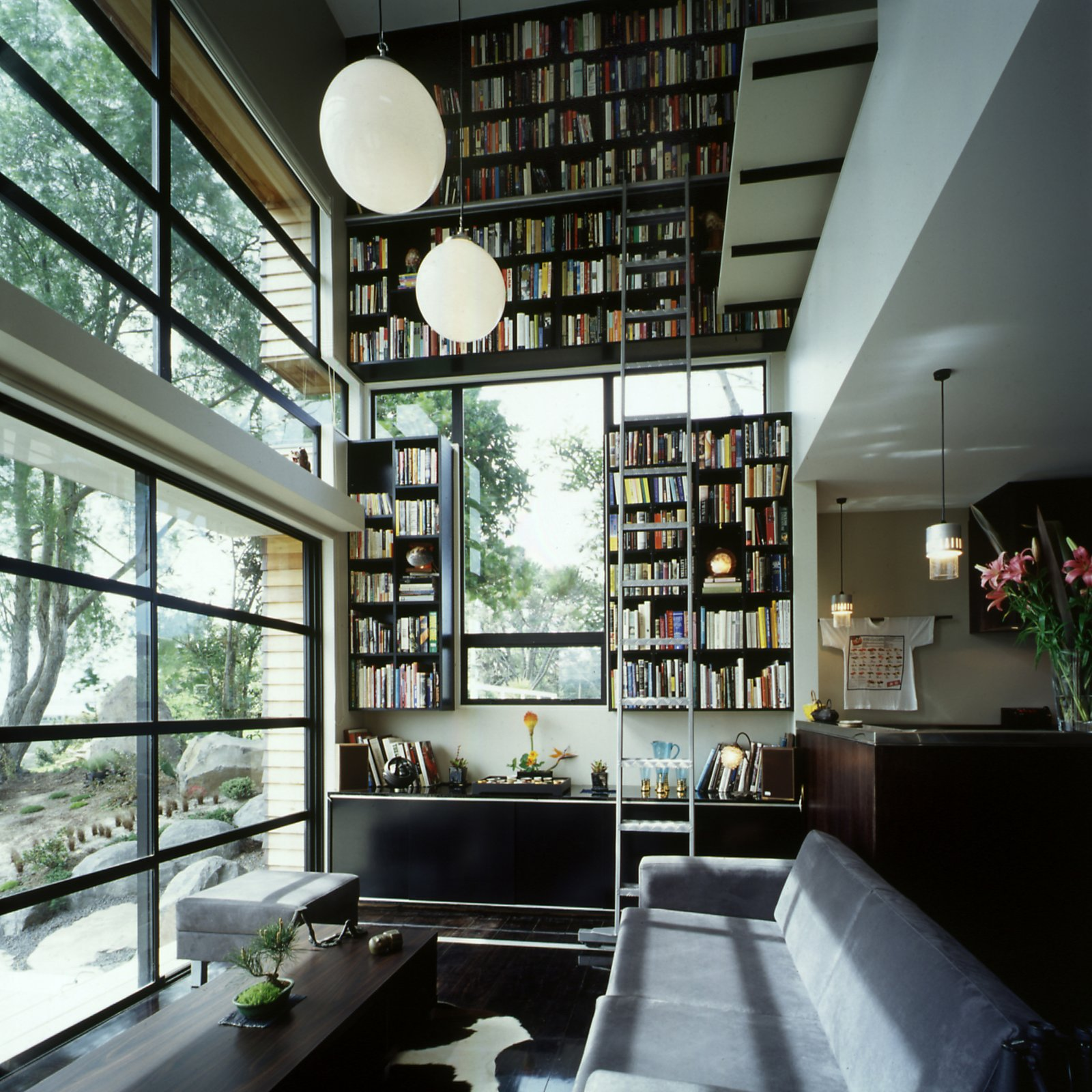 When architect Andrew Lister designed this wedge-shaped, Japanese-style house outside of Auckland for actor Yuri Kinugawa and film producter Owen Hughes, he wanted to make the interior feel larger than it was. The vertiginous two-story bookcase that takes up the entire northern wall of the living room draws the eye upwards, adding spacial impact without taking up any floor space.  Gigantic Home Libraries by William Harrison